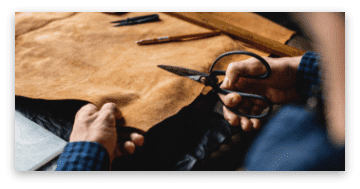 Closeup of craftsman cutting leather